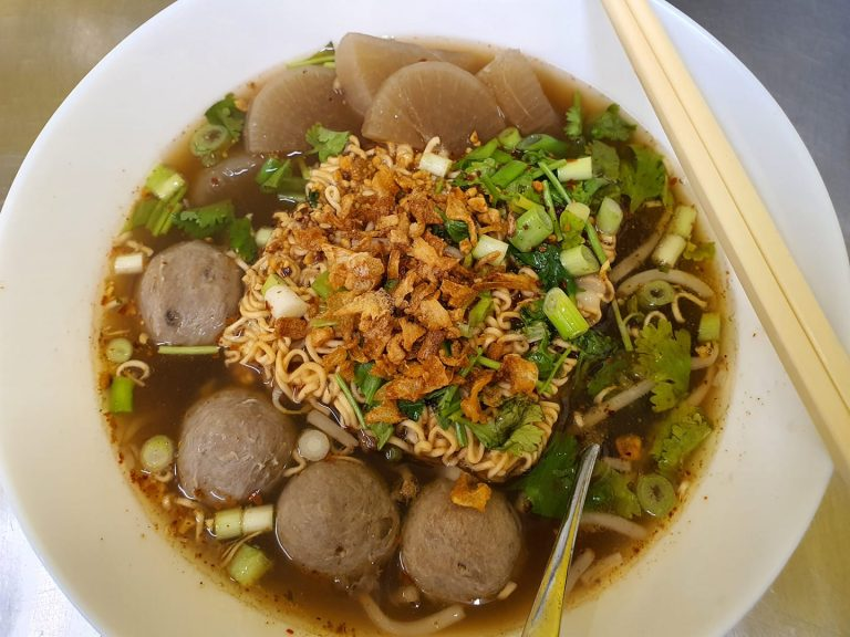 beef noodle soup with meatballs, spring onions, in bowl with chopsticks