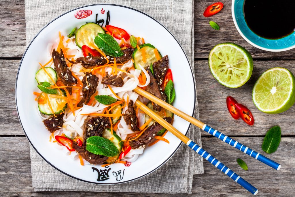 stir fried beef with noodles and salad