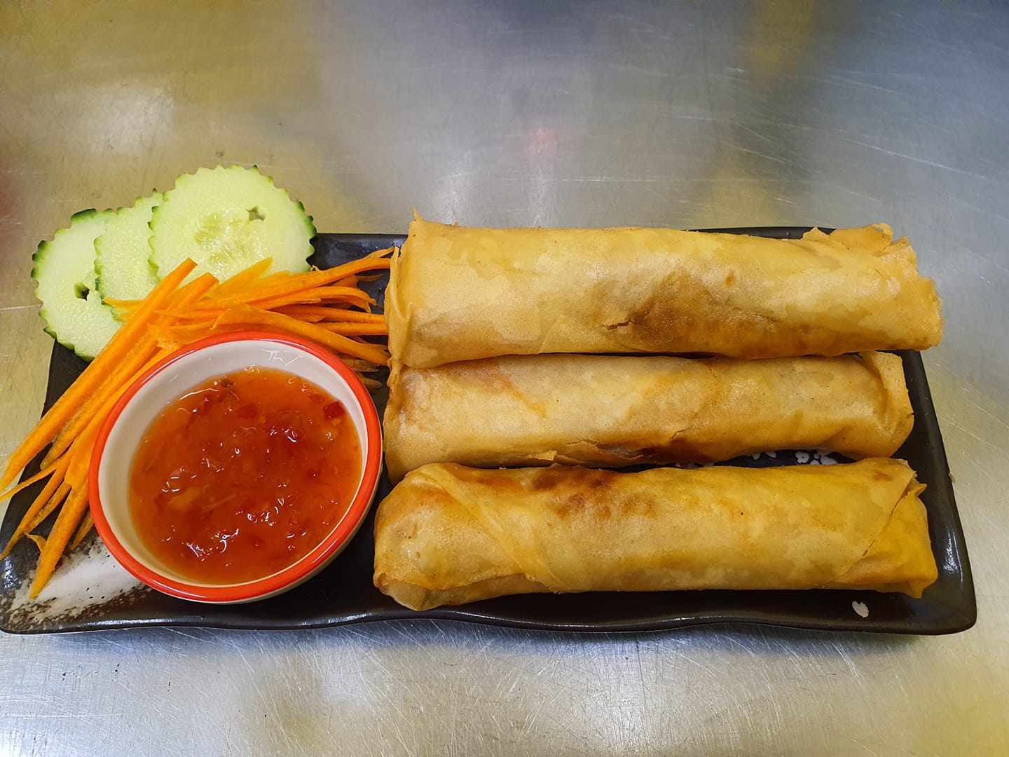 crisspy fried thai spring rolls served with sweet chili sauce cucumber and carrots