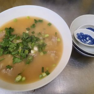 clear thai soup with corriander and large soup spoon in bowl